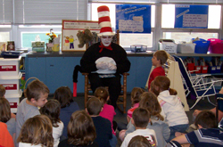 Employee visiting elementary classroom dressed as Cat in the Hat