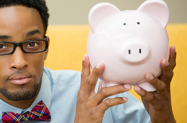 Business man holding a pink piggy bank
