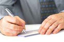 Photo of a businessman signing a check