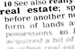Photo of the inside of a dictionary of the word real estate