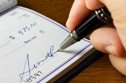Image of someone signing their name on a check from checkbook