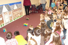 Photo of elementary school children cheering on battery-operated pigs racing on the carpet