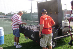 Photo of two men grilling on a huge gas grill