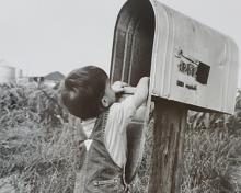 young boy getting the mail