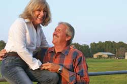 Husband and wife laughing on a country fence, enjoying retirement